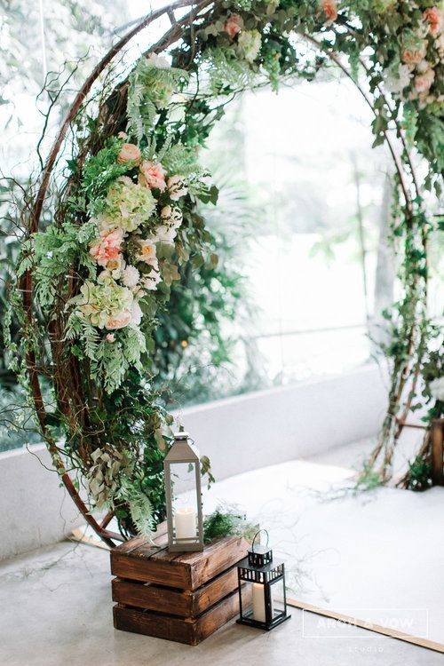 A rustic wedding arch with green and pink blooms paired with a candle lamp