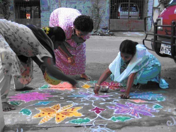 Vrouwen maken een kolam voor hun huis in India