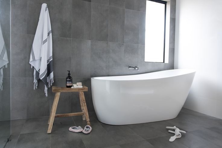 Red Lily Renovations. Large bathroom renovation. Vertically laid grey tiles lengthen the space and the white wall bounces light giving it a larger feel. Stool from Antedote Living, Mt Hawthorn. Turkish Towel from Kmart. Kado Freestanding bath from Reece Bathrooms