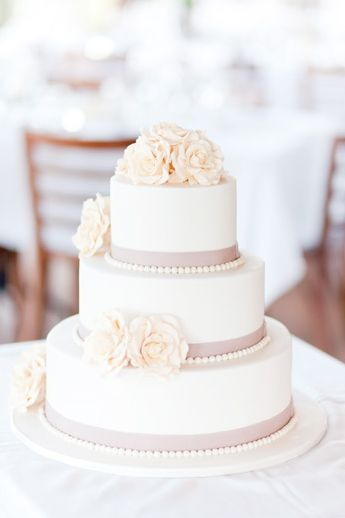 Vintage Rose Wedding Cake in white and cream with a dusty pink satin ribbon.