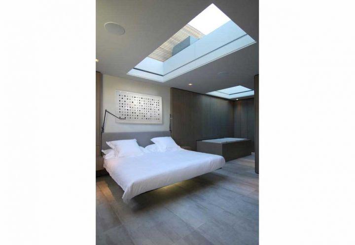 Gusto chic per la spaziosa zona notte del sottotetto riqualificato a Londra da Cousins & Cousins: i pavimenti in parquet di rovere spazzolato, l'ampio lucernario, il letto sospeso di Scossa e la vasca idromassaggio contribuiscono all'atmosfera intima e raffinata