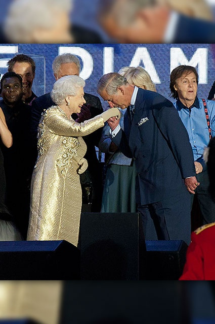 Prince Charles, Prince of Wales kisses the hand of his mother Queen Elizabeth II as she is joined on stage by the rest of the Royal family as well as performers during the Diamond Jubilee, Buckingham Palace Concert on June 04, 2012 in London, England.