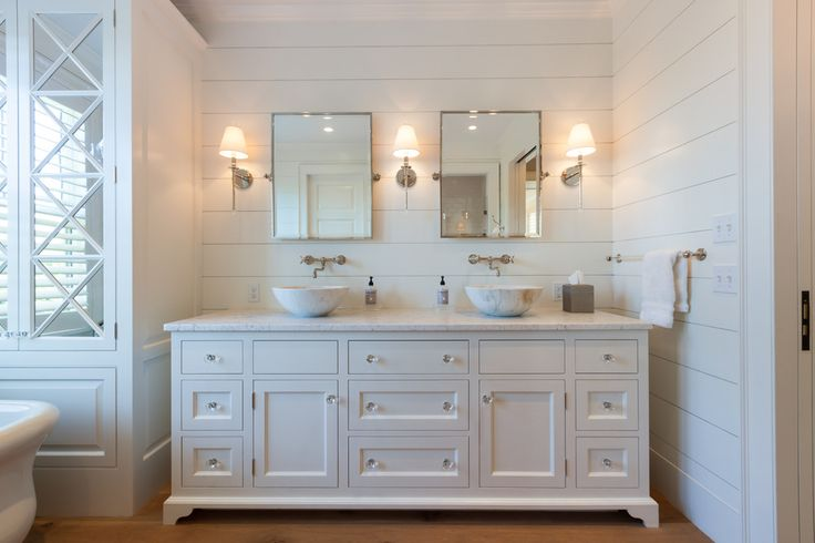 shiplap Beach Style Bathroom Designs Boston crystal knobs dual sinks glass-front cabinets nantucket style tilt mirrors towel bar vanity wall sconces white bathroom white paneling