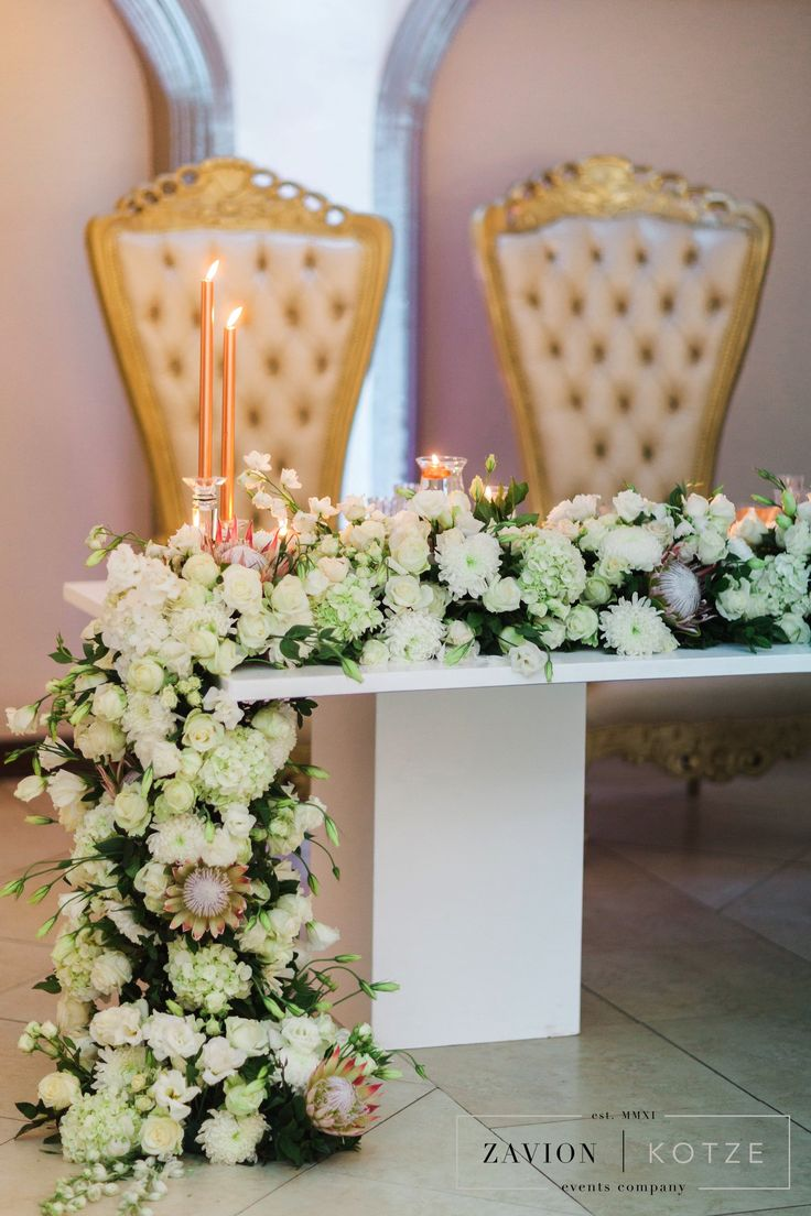 White roses, orchids mass arrangements, rose gold candles