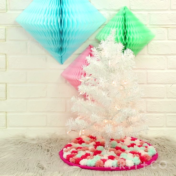 You can make a Christmas tree pom pom skirt by following this easy festive holiday video DIY tutorial.