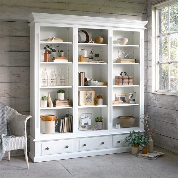 Burford Grand Bookcase from The Cotswold Company. Free Delivery & Free Returns No book lover will be able to resist the alluring charms of this impressively proportioned bookcase. Making a magnificent focal point in any room large enough to handle it, there are three tall rows of adjustable shelving to look after your book collection, topped with an elegant tapered cornice. It also has three spacious dovetailed drawers at the bottom for extra storage space.