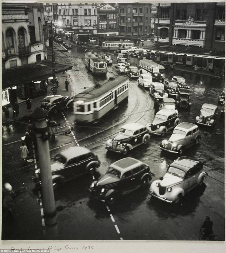 Pictured are trams and automobiles racing through the streets and around a corner during rush hour in Kings Cross in 1938