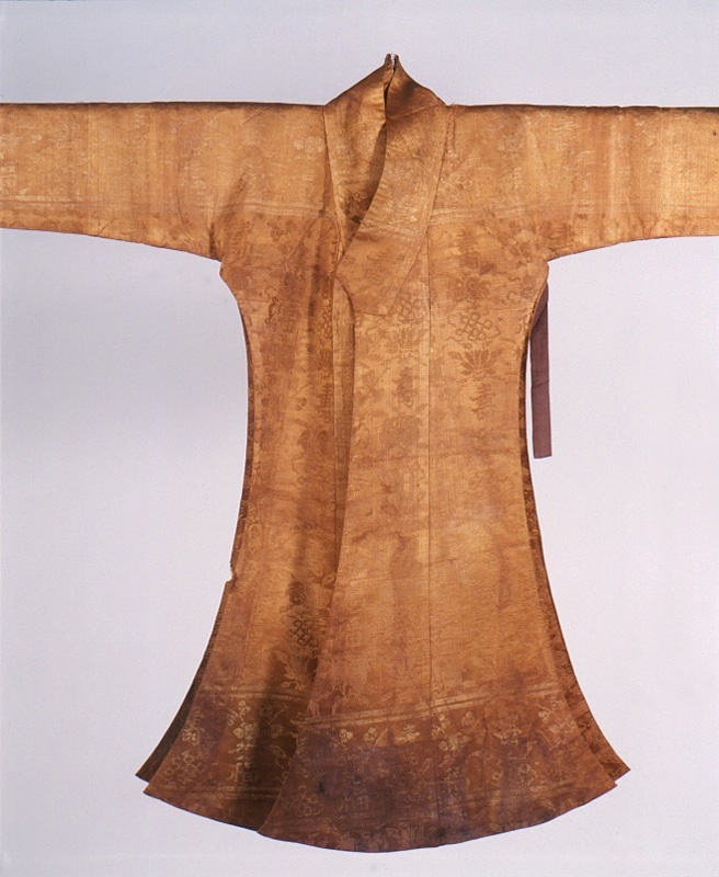 Dang-ui (당의, 唐衣), knee-length jacket, open at the sides, for court-wear. Silk brocade fabric with purple breast ties. From the reign of King Seonjo (ruled 1567-1608). Important Folklore Material 57. It is decorated with the characters for 'long life', 'happiness' and the patterns of the seven treasures, pomegranates peonies on a light brown ground.