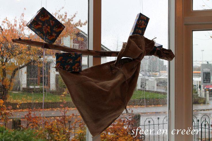 Aan een grote tak een sinterklaas jute zak opgehangen met een paar sinterklaas kado's.