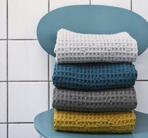 Serviette de toilette et drap de bain en coton organique bio décliné dans 3 couleurs typique de la marque Ferm Living : jaune moutarde, bleu pétrole et gris clair pour une salle de bain scandinave
