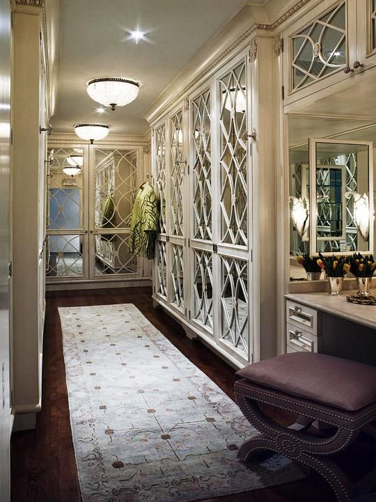Glamorous ivory walk-in closet with mirrored doors, blue & brown Oriental runner rug, vanity and purple linen bench with nailhead trim.
