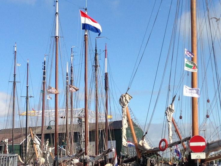 The masts of the historic fleet in the port of Monnickendam with a  dutch blue sky
