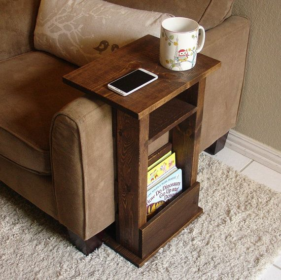 Handcrafted tray table stand with storage pocket. The perfect addition to a sofa chair in any home, apartment, condo, or man cave. It has been sanded down, then stained and sealed with a dark walnut finish. The stand is free standing and can be used anywhere around the house. Non-marking, non-skid rubber pads are installed on the bottom of the base. This piece does not include the accessory items as shown in the pictures. The color of the stained wood captured in the photos might vary sli...
