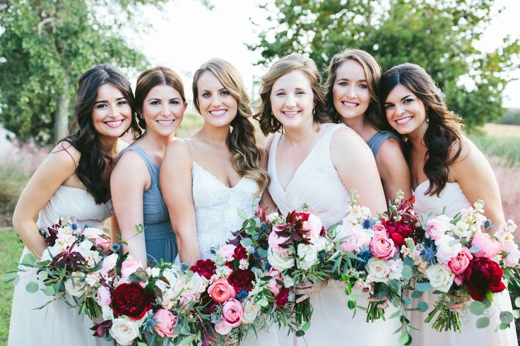 bride and her maids in grey and blush hold their loose and organic bouquets of red charm peony, romantic antique garden rose, white majolik spray rose, blue thistle, light pink ranunculus, white astilbe, peach stock, quicksand rose, seeded eucalyptus, willow eucalyptus & jasmine vine.
