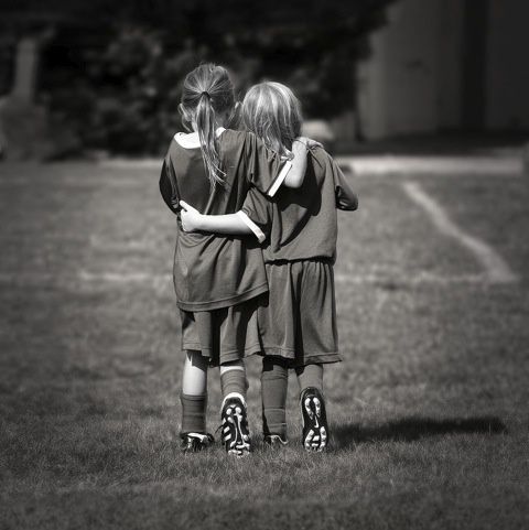 BW picture of to young soccer players, being pals.