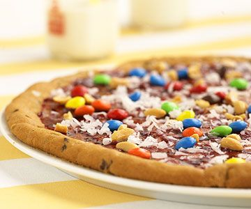 Chocolate-Chip Cookie Pizza. It's a giant chocolate chip cookie topped with frosting, candy, and peanuts. This version is covered with Coconut, Candy-coated Chocolate, and Peanuts.