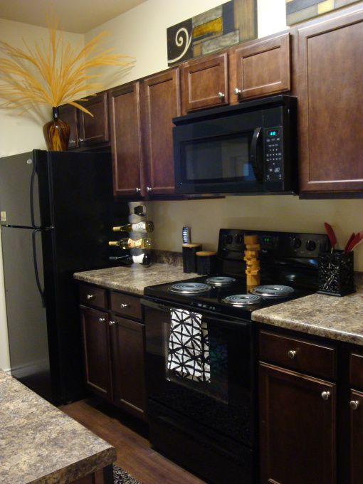 This layout could work for the backside of the kitchen. Dark cabinets look nice too, but with the silver rod looking slender handles.