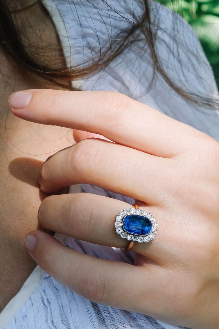 Antique Victorian ring with 4 carat natural Ceylon oval-cut sapphire center, surrounded by 18 round diamonds set in platinum and gold. Circa 1880