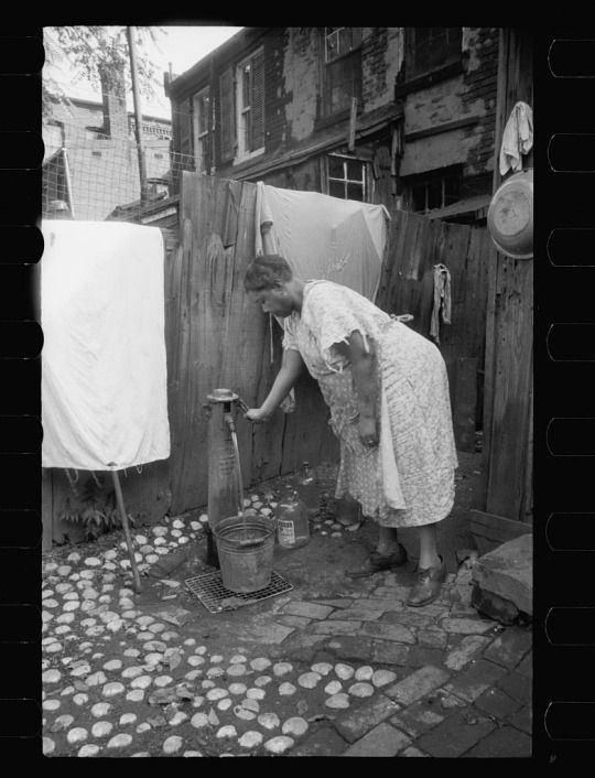 Lady getting water from outside water supply shared by a set of slum houses in Washington DC, 1935.