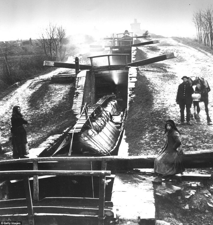 A woman perches on the locks while another drags a canal boat and a man watches on with hi...
