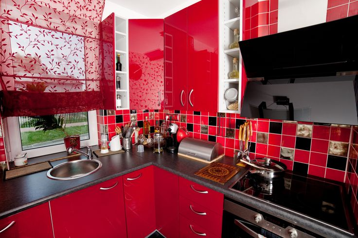 Glossy red kitchen cabinets were even livelier with the addition of black and red tiling on the wall and red lace curtains.