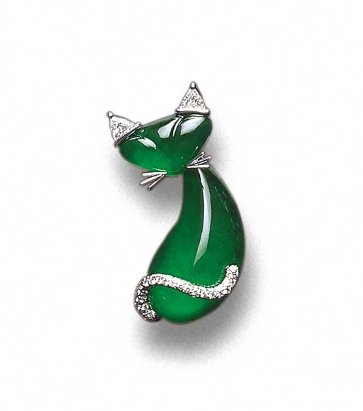 Christie's -  Broach.   Designed as a Siamese cat, with a drop-shaped cabochon body and a near triangular head, both of translucent vivid emerald green jadeite material, its spine and face subtly defined, with triangular-cut diamond ears and a pavé-set diamond scrolling tail, mounted in 18K white gold,