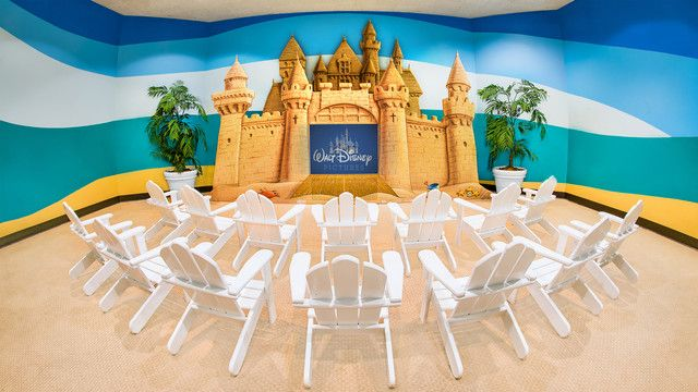 Adirondack chairs surround a model of a castle with a large screen television positioned in its entrance