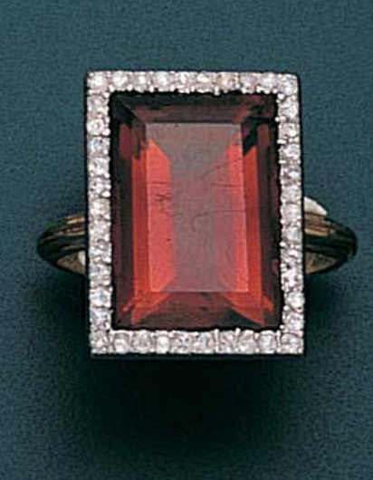 A citrine and diamond ring, circa 1905  The rectangular step-cut citrine of burnt orange colour, within a border of rose-cut diamond points, the bezel engraved with trefoil motifs, two diamonds deficient, engraving to interior of hoop partially obscured `Georgette [?] 1908`