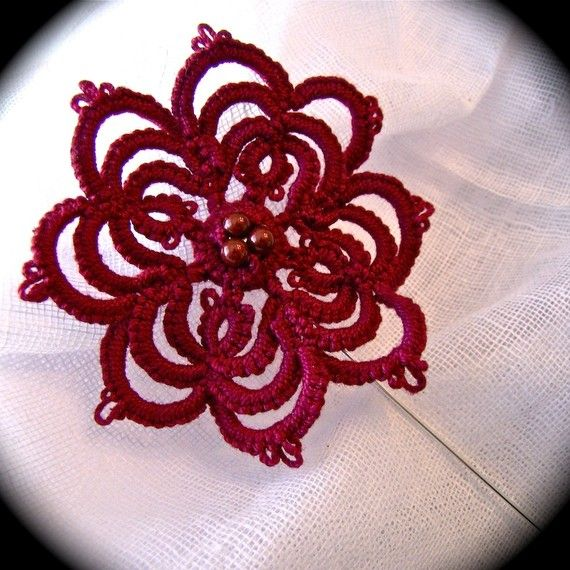 Using an old illustration as a guide, I tatted up this striking lace flower. I used high quality burgundy red cotton thread and tatted it directly onto