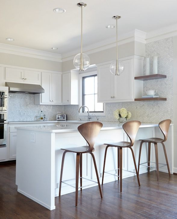 White kitchen with shapely wood counter stools