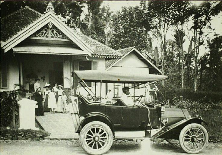 Portret van een familie voor een villa met op de voorgrond een auto met chauffeur. Bandoeng 1880-1935