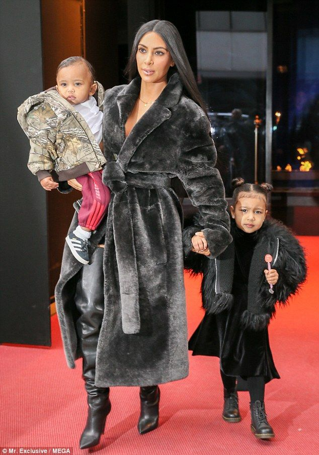 Runway ready: Kim looked chic in a long black velvet robe coat with matching thigh-high le...