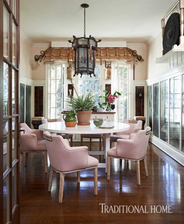 Light pink chairs circle around the bleached oak dining table in the breakfast room. Overhead, an original chandelier brings the drama. - Photo: Dominique Vorillon / Design: Jennifer Culp