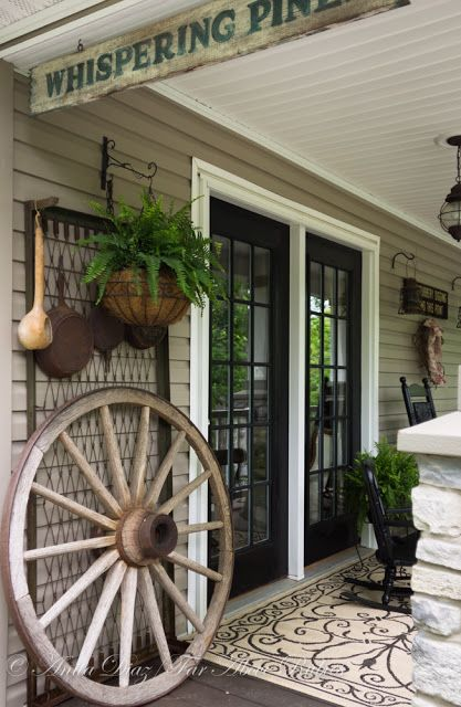 An old wagon wheel adds more visual interest to an otherwise overlooked nook, and a vintage bedframe—stood upright—is a clever spot to hang vintage pots and pans.