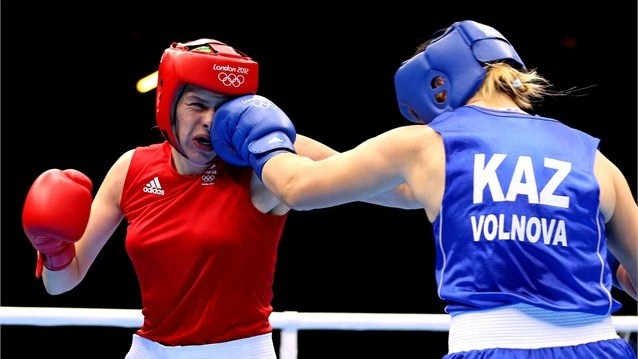 Marina Volnova of Kazakhstan (Blue) competes against Savannah Marshall (Red) of Great Britain during the Women's Middle (75kg) Boxing Quarterfinals on Day 10