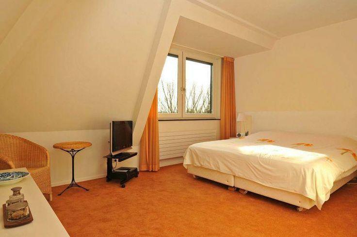 De master bedroom met vrolijk oranje tapijt en bijpassende gordijnen. Godelindeweg 1A 37, Naarden.