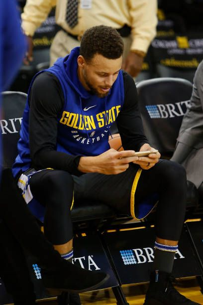 Stephen Curry of the Golden State Warriors looks on from the bench during warm ups before the game against the Denver Nuggets at ORACLE Arena on...