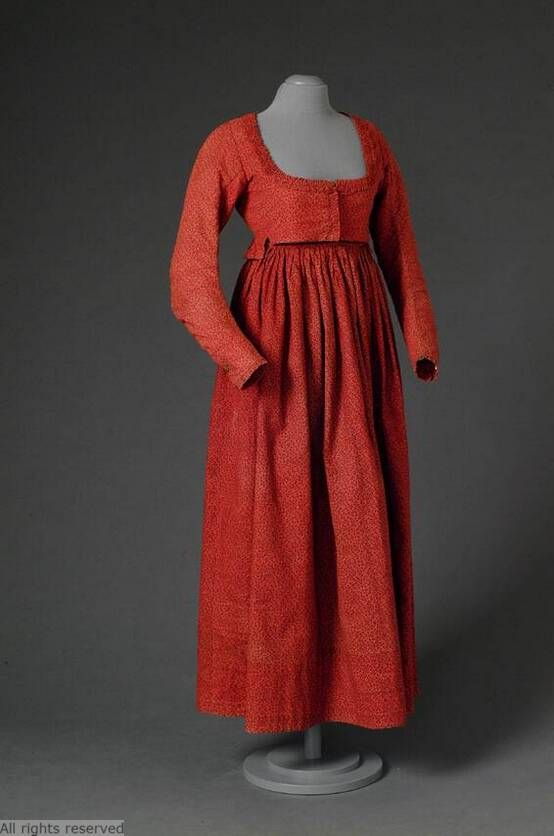 1800-1820  Corsage in red cotton printed with black flower sprigs Short model with lap building in the back; low, square neckline; long sleeves appropriate; closes mid front with hooks and eyes; lined with coarse linen.