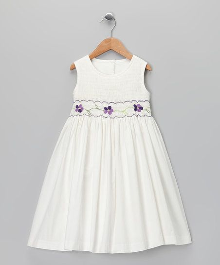 As beautiful as a rose in bloom, this elegant dress is adorned with hand-smocking and a billowing skirt that will dance at every step, skip and sashay. An opening at the back also makes this piece extra simple to put on.