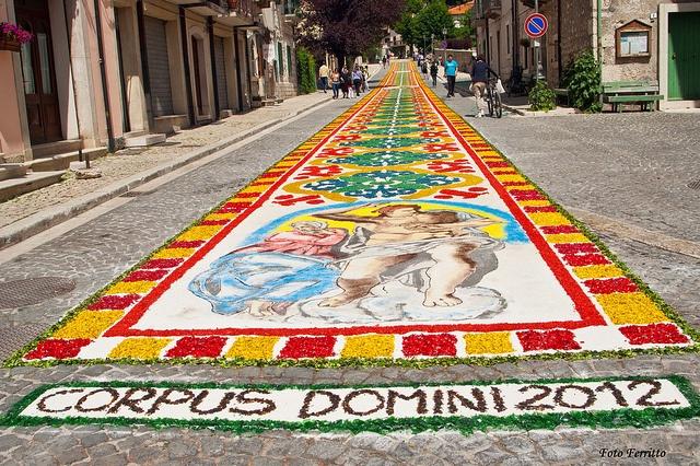 We Włoszech przeniesiono obchody Bożego Ciała z czwartku na niedzielę po. Tradycją stało się dekorowanie trasy procesji Bożego Ciała kwietnymi dywanami. W środę zespoły tworzące dywany zbierają kwiaty i zioła, których płatki dzielą według kolorów. Rozłożone na ulicy rysunki w ciągu nocy są wypełniane owymi płatkami kwiatów i ziół. Prace trwają do rana. Wzory dekoracji nigdy się nie powtarzają.  Na zdjęciu zeszłoroczny kobierzec w Pescasserola (Abruzzo)