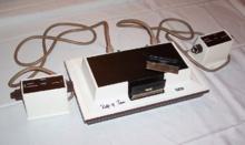 """Comercializada por la filial de Philips en Estados Unidos, la Magnavox Odyssey es la primera videoconsola de la historia. Fue desarrollada por Ralph Baer (apodado """"el padre de los videojuegos caseros"""") y lanzada en las tiendas norteamericanas a finales del año 1972, convirtiéndose en un éxito de ventas en muy poco tiempo.  Sus juegos (veintiocho títulos diferentes en total) eran de una sencillez extrema: ping-pong, """"tenis de mesa"""", voleibol, etc."""