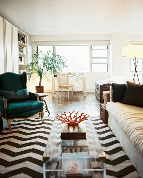 chevron rug topped with a transparent trunk and a green armchair
