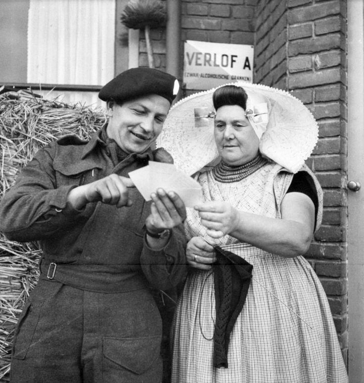 Canadian Trooper K. Kosak, of Winnipeg's The Fort Garry Horse, 38 Canadian Brigade Group, shows a Dutch woman photographs from home. Goes, Zuid-Beveland, Zeeland, Netherlands. 1 November 1944. Image taken by Canadian Army Lt. Ken Bell.