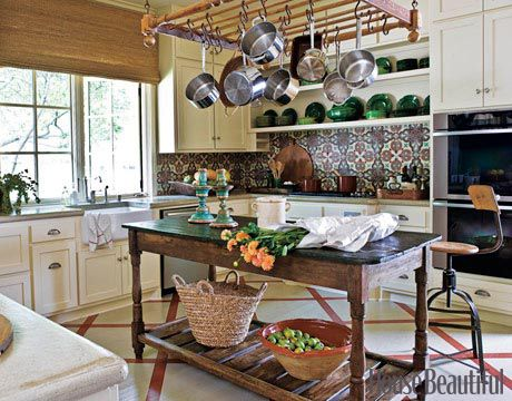 French Provincial Kitchen  The French candlesticks and the 1940s French faience on the open shelves echo the green in the backsplash, made of 19th-century French concrete tiles. Designed by Shannon Bowers.