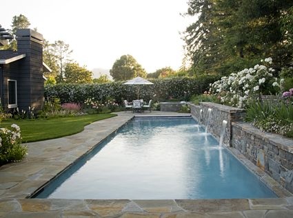 When the lap pool is not being used for swimming, the fountains provide a focal point and a relaxing acoustic backdrop that compliments the lively garden planting. This client renovated their existing home in Orinda with the goal of graceful, easy outdoor entertaining in mind. Into this relatively small backyard, we artfully crafted a space for a lap pool with fountains and raised spa. Architect: Bayfront Architecture and Planning