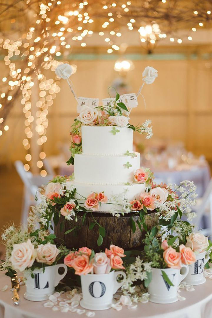 Pretty cake display with love mugs filled with flowers, the rustic cake stand adorned with flowers and the petals on the table ~ we ❤ this! moncheribridals.com