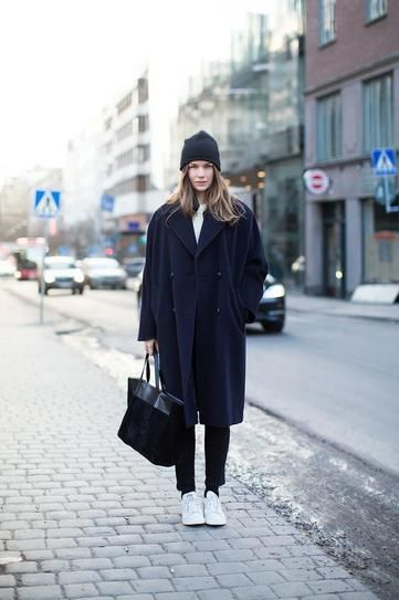 Street Style: Navy fall coat worn with a beanie, black trousers, and white Adidas sneakers.