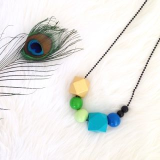 This gorgeous necklace is exclusively made for Brindie! Beautifully handmade wooden geobead necklace featuring all of the colours found in peacock feathers - gold, black, light and dark green, turquoise & cobalt blue.   The necklace is comprised of 7 geometric and spherical beads ranging in size from 8mm-30mm.    Each bead is painted in lovely silky acrylic and finised with several coats of non-toxic varnish to ensure it is safe to be worn next to perfume.   As the beads are hand painted...