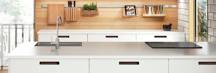 Väggplatta i trä samt metallstång med köksredskap bakom två stycken måttbeställda vita bänkskivor.