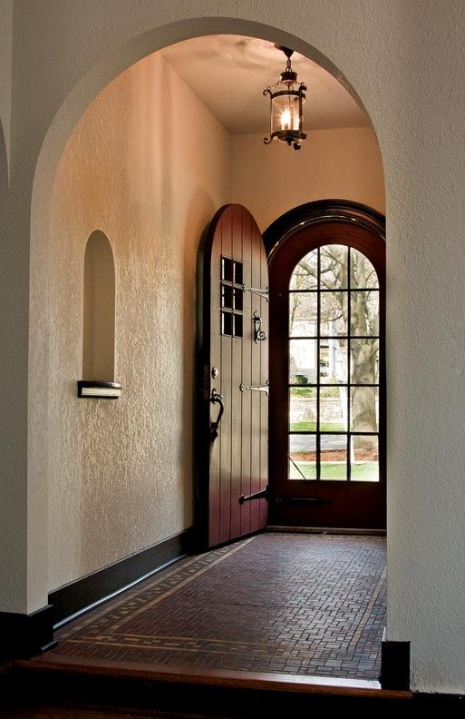 spanish styling for entry way and door. love the niche, the door, the ceiling light, the screen door, the flooring.